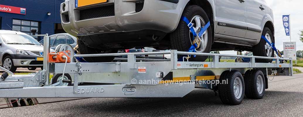 Autotransporter met SUV op laadvloer vastgezet met spanbanden