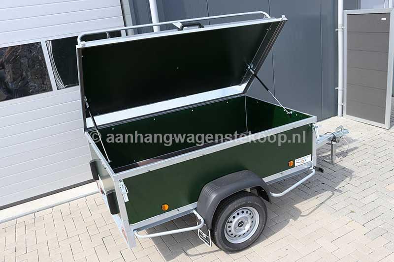 Bagagewagen met groen betonplex panelen en geopend deksel