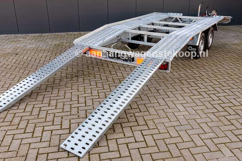 Tandemas autotransporter met open laadvloer en oprijplaten