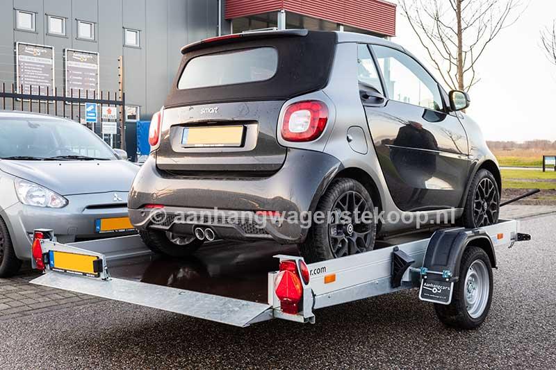Kleine zakbare autotransporter met Smart op de laadvloer