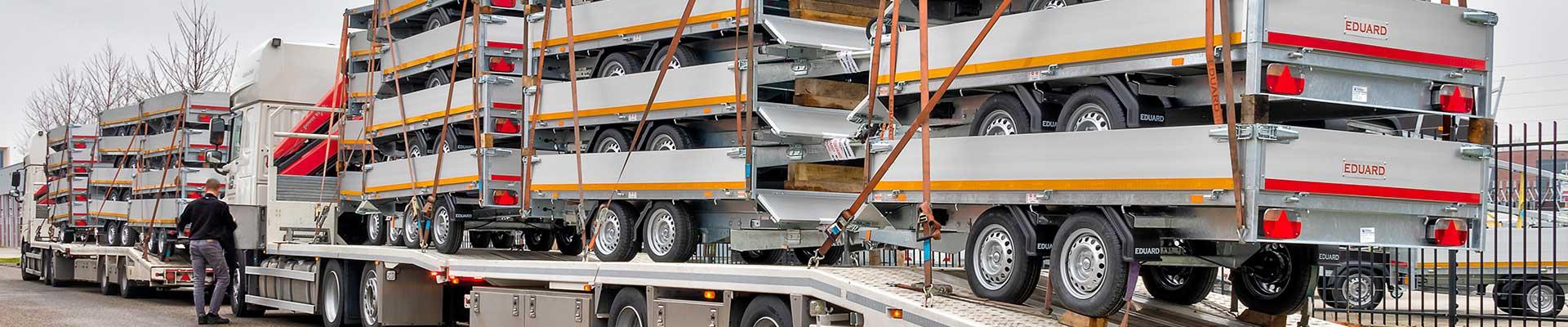 Twee vrachtwagens met nieuwe aanhangwagens voor de voorraad